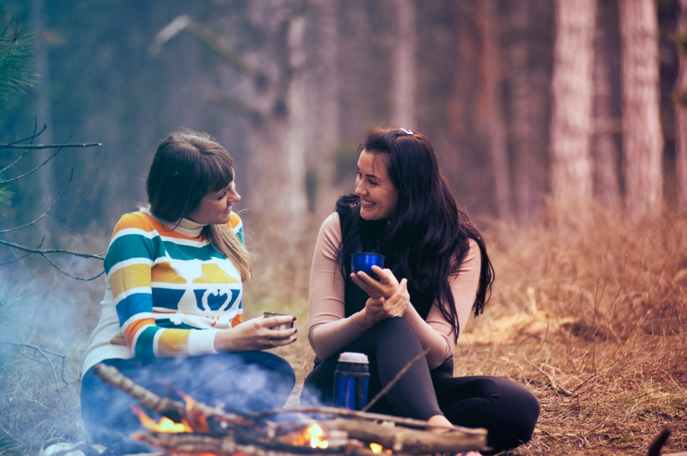 Two girls talking by camp fire